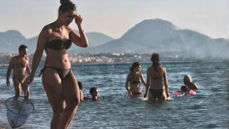 Παραθεριστές προσπαθούν με απόχες να καθαρίσουν τη θάλασσα από τις τσούχτρες