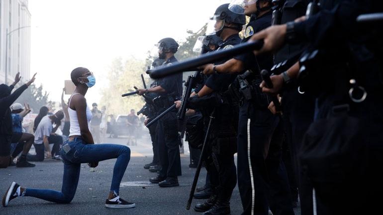 ΗΠΑ: Διαδηλώτρια που γονάτισε μπροστά στο «τείχος» των αστυνομικών έγινε viral