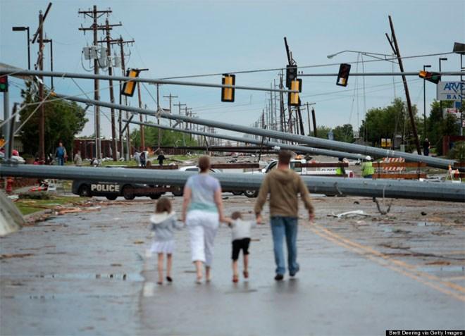 21 Μαΐου. Μία οικογένεια περπατά στη λεωφόρο Σάντα Φε, στο Μουρ της Οκλαχόμας, μετά το φονικό πέρασμα τυφώνα που άφησε πίσω του 23 νεκρούς, εκατοντάδες τραυματίες και υλικές ζημιές που εκτιμώνται στα 2 δις δολάρια.