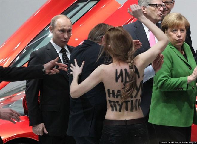 8 Απριλίου. Μία διαδηλώτρια - μέλος της φεμινιστικής οργάνωσης «Femen» αντιμετωπίζει τόπλες τον Ρώσο πρόεδρο Βλαντιμίρ Πούτιν κατά τη διάρκεια της επίσκεψής του με τη Γερμανίδα καγκελάριο Άνγκελα Μέρκελ σε μία έκθεση αυτοκινήτων. Η έκφραση του Πούτιν κλέβει την παράσταση.