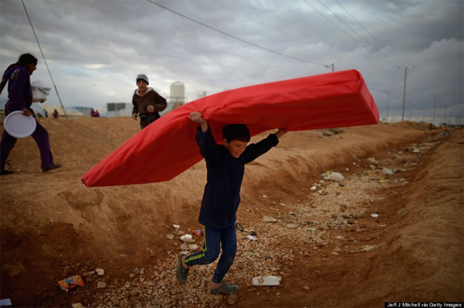 29 Ιανουαρίου. Ένας νεαρός πρόσφυγας από τη Συρία, χαμογελά παίζοντας με ένα κόκκινο στρώμα. Το αγόρι ζούσε σε καταυλισμό προσφύγων στο Mafrq της Ιορδανίας.