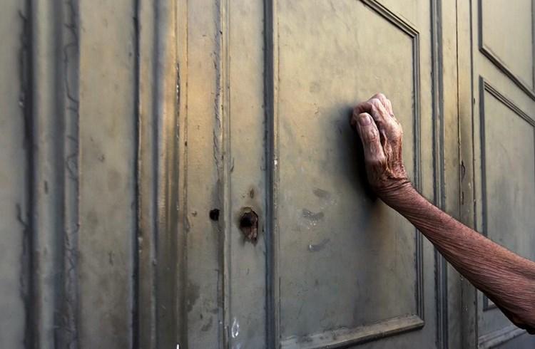 Συνταξιούχος ακουμπά στην πόρτα τράπεζας, περιμένοντας στην ουρά για να πάρει ποσό από τη σύνταξή του, Αθήνα, Ιούλιος 2015/Γιάννης Μπεχράκης