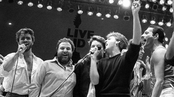 1985 – Στο στάδιο Wembley του Λονδίνου, στη φιλανθρωπική συναυλία «Live Aid famine relief» μαζί με τους Harvey Goldsmith, Bono, Paul McCartney, Bob Geldof και Freddie Mercury.