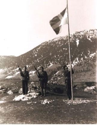 Έπαρση σημαίας στην Αγόριανη (Μάρτιος 1943). Όπλα παρουσιάζουν –με τον αντάρτικό τρόπο που είχε καθιερώσει ο Άρης- ο Χ, Κουρέλης από τη Λαμία, και ο Γ. Μέτος από τη Στρώμη. Στη σημαία ο Νικηφόρος.