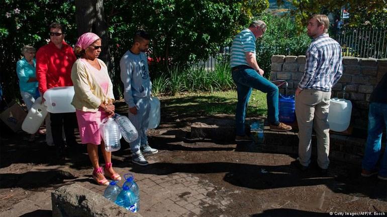 Πολίτες στέκονται στην ουρά για να γεμίσουν τα μπουκάλια τους με νερό