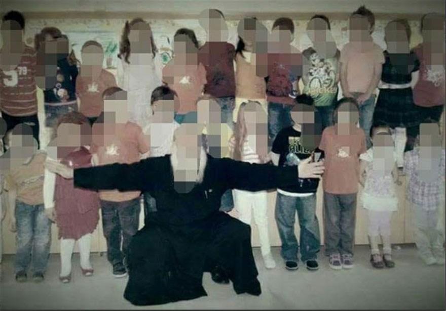 Φωτογραφία του ιερέα με παιδιά από το σχολείο δίπλα στο οποίο διαμένει