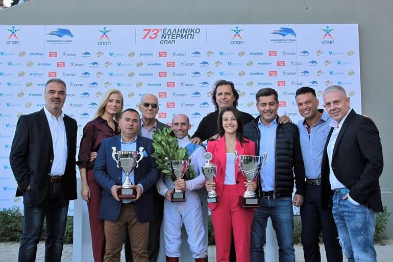 Ο Διευθυντής Πωλήσεων TASTY, Ηλίας Ξηντάρας με την Ευαγγελία Αραβανή, τους εκπροσώπους της προπονήτριας Ντίνο και Άννα Γεωργίου, το μέλος του Δ.Σ. της ΦΕΕ, Μάκη Σκρεπετό, τον αναβάτη Γιάννη Λαζαρίδη, τον πρώην διεθνή ποδοσφαιριστή Τάσο Μητρόπουλο, τον αναπληρωτή Διευθύνων Σύμβουλο ΟΠΑΠ, Οδυσσέα Χριστοφόρου, τον Κώστα Σόμμερ και τον Ιδιοκτήτη της ΔΟΥΣΗΣ COM Τάσο Δούση